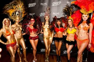 Body-painted and feathered showgirls pose on the red carpet for guests attending the Midsummer Lingerie Carnival at Palms Pool in Las Vegas on Saturday, Aug. 17, 2013.