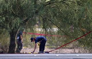 A crime scene analyst looks over a scene as Henderson Police investigate an officer-involved shooting near Boulder Highway and College Drive in Henderson, Aug. 20, 2013.