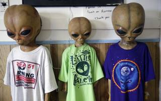Alien dummies model t-shirts for sale along with other extraterrestrial-themed souvenirs at the Little A'Le'Inn, located nine miles up the road from the military testing base known as Area 51, in Rachel, Nev., Aug. 20, 2013. Last week, the CIA released a classified report officially confirming the existence of the military testing base famously rumored to have researched UFOs and alien life, though residents of the area have long known about it.