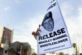 A protester holds up a flier in support of Army Pfc. Bradley Manning in front of the Lloyd George Federal Building in downtown Las Vegas Wednesday, Aug. 21, 2013. A military judge sentenced Manning to 35 years in prison for leaking hundreds of thousands of classified documents to WikiLeaks.
