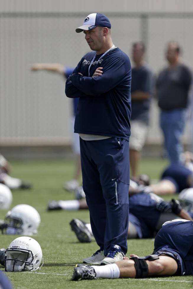 Penn State head football coach Bill O'Brien watches his team stretch during the NCAA college football team's practice in State College, Pa., Thursday, Aug. 8, 2013.