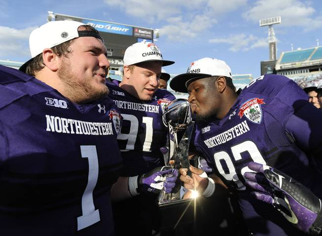 Northwestern defensive lineman Brian Arnfelt (91) and Bo Cisek (1) holds the trophy while their teammate Will Hampton (92) kisses it after the Gator Bowl NCAA college football game against Mississippi State, Tuesday, Jan. 1, 2013 in Jacksonville, Fla. Northwestern won 34-20.
