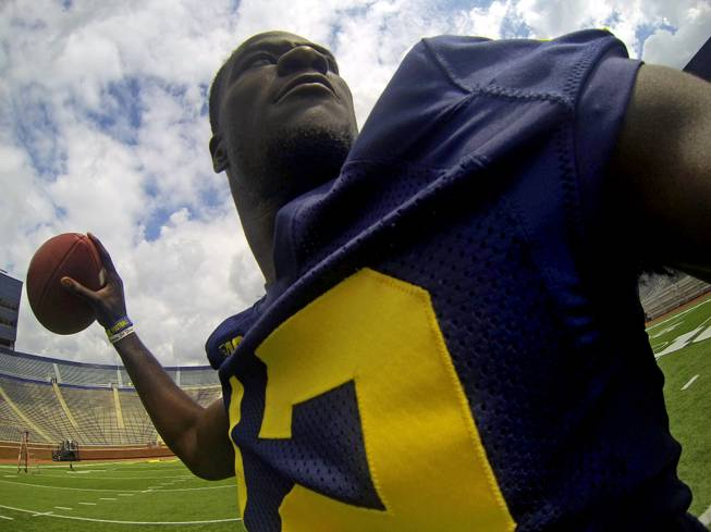 Michigan quarterback Devin Gardner captures a self-portrait from an arm-worn camera as he throws passes in Michigan Stadium during the NCAA college football team's annual preseason media day on Sunday, Aug. 11, 2013, in Ann Arbor, Mich.