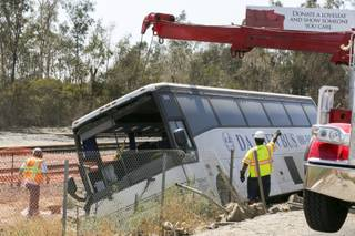 Salvage towing crews remove an overturned tour bus carrying gamblers to a casino on the 210 Southern California freeway injuring more than 50 people on board in Irwindale, Calif., on Thursday, Aug. 20, 2013.