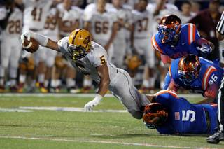 Mountain Pointe running back Wesley Payne stretches for yards while being tackled by Bishop Gorman's Ryan Garrett during their Sollenberger Classic game at Bishop Gorman Friday, Aug. 13, 2013.