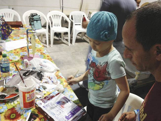Junaisy Vargas, 5, paints a box with her father, Otoniel Vargas, at Kaiden Bresgi-Goffard's 11th birthday on Saturday, Aug. 23, 2013. Junaisy recently completed chemotherapy for a tumor and is in the Cure 4 the Kids program, which helps children with genetic disorders and rare illnesses.