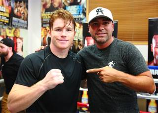 Boxer Canelo Alvarez, left, of Mexico poses with Oscar De La Hoya in Big Bear, Calif. Tuesday, August 27, 2013. Alvarez will face undefeated boxer Floyd Mayweather Jr. in a WBC/WBA 154-pound title fight at the MGM Grand Garden Arena in Las Vegas on September 14. Hogan Photos/Golden Boy Promotions