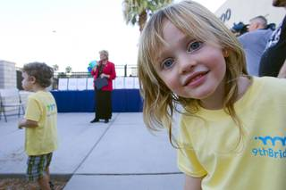 Mia Castellarin, 4, looks at the camera as Las Vegas Mayor Carolyn Goodman, center, speaks during a grand opening ceremony for the 9th Bridge School in downtown Las Vegas Tuesday, Aug. 27, 2013. The private school/early childhood learning center, part of the Downtown Project, opened August 26 with infants through kindergarten students and will gradually add grades.