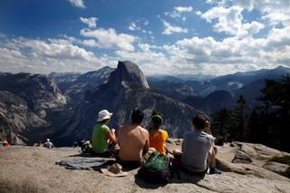 Tourists enjoy the view at Glacier Point in California's Yosemite National Park on August 27, 2013, as the Rim fire continues to rage about 25 miles away. As the devastating fire spreads deeper into Yosemite, would-be park visitors are having to decide whether to cancel plans made months or years in advance or press ahead with a visit that could potentially end in a smoky evacuation. Many are choosing to keep their date with El Capitan and Half Dome.