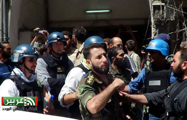 In this citizen journalism image provided by the United media office of Arbeen which has been authenticated based on its contents and other AP reporting, UN investigation team with blue helmets, walk with Syrian rebels in Damascus countryside of Zamalka, Syria, Wednesday, Aug. 28, 2013.