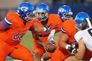 Bishop Gorman quarterback Randall Cunningham looks to hand off to a teammate during Gorman's 41-17 win over Servite Friday, August 30, 2013.