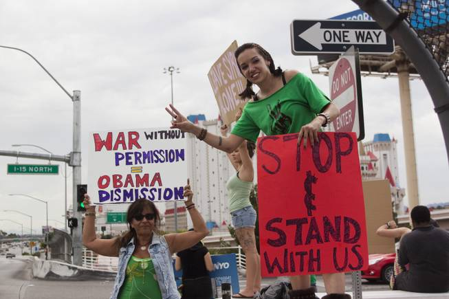 People hold up peace and anti-war signs during a protest against U.S. intervention in Syria held on Tropicana and the I-15, Saturday, Aug. 31, 2013.