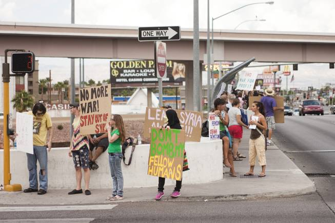 Protesters against U.S. intervention in Syria line the sidewalk on Tropicana and the I-15, Saturday, Aug. 31, 2013.