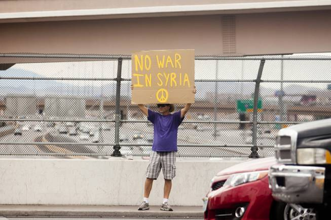 "A man holds up a ""No War In Syria"" sign during a protest against U.S. intervention in Syria held on Tropicana and the I-15, Saturday, Aug. 31, 2013."