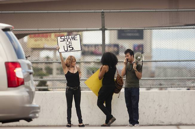 "A woman holds up a ""Sham on U.S."" sign to oncoming traffic during a protest against U.S. intervention in Syria held on Tropicana and the I-15, Saturday, Aug. 31, 2013."
