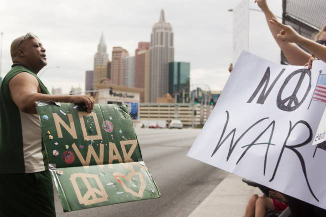 People hold up anti-war signs during a protest against U.S. intervention in Syria held on Tropicana and the I-15, Saturday, Aug. 31, 2013.
