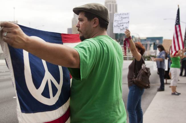 A man holds up a peace flag during a protest against U.S. intervention in Syria held on Tropicana and the I-15, Saturday, Aug. 31, 2013.