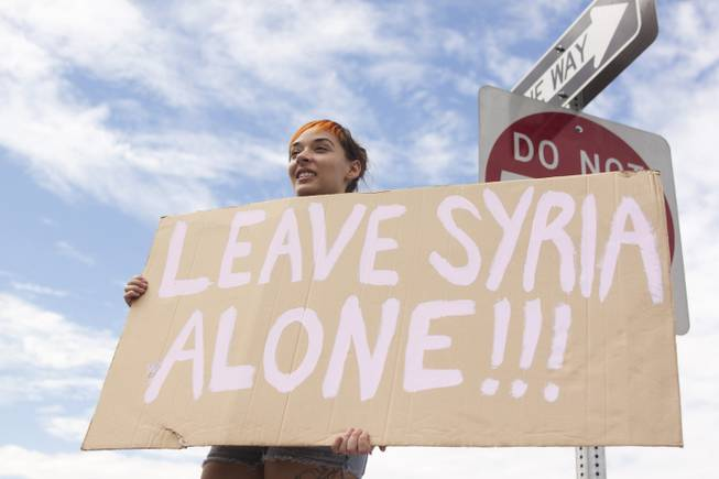 "Morgan Pavlich hold up a ""Leave Syria Alone"" sign during a protest against U.S. intervention in Syria held on Tropicana and the I-15, Saturday, Aug. 31, 2013."