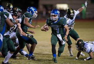 Gators quarterback Christian Lopez scrambles out of a collapsing pocket as a play breaks down during a game against the Basha Bears at Green Valley High School on Friday night.