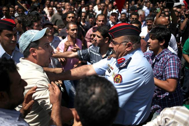 A Jordanian man, left, chants anti-President Bashar Assad slogans as a police officer pushes him away to separate him from opposing protesters from the Jordanian Communist Party and other leftist groups against any American military strike against Damascus, in Amman, Jordan, Friday, Aug. 30, 2013.