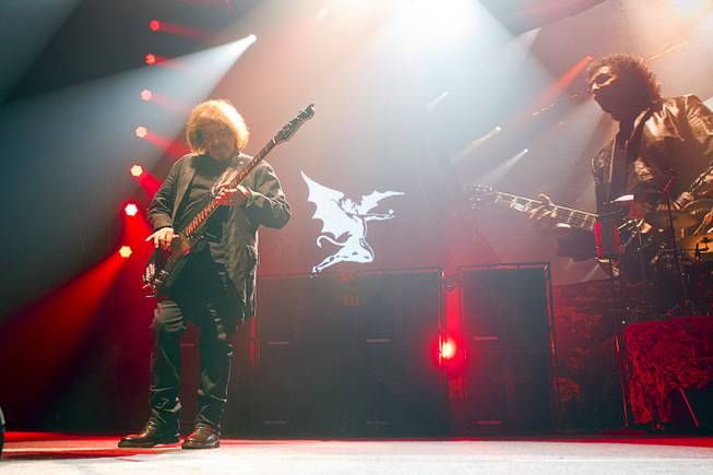 Black Sabbath bassist Geezer Butler performs at MGM Grand Garden Arena on Sunday, Sept. 1, 2013. A live projected image of guitarist Tony Iommi is at right.