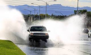 A car drives through a flooded area on Sunset Road on Monday, September 2, 2013. The National Weather Service issued a flash flood warning for areas of Henderson late in the afternoon.