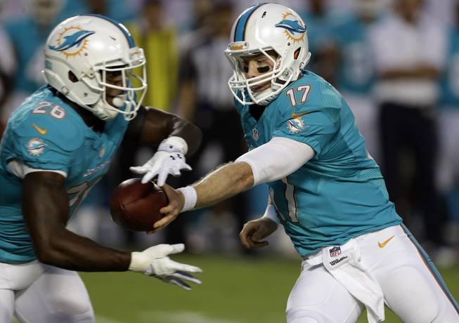 Miami Dolphins quarterback Ryan Tannehill (17) passes to running back Lamar Miller (26) during the first half of an NFL preseason football game against the Tampa Bay Buccaneers, Saturday, Aug. 24, 2013, in Miami Gardens, Fla.