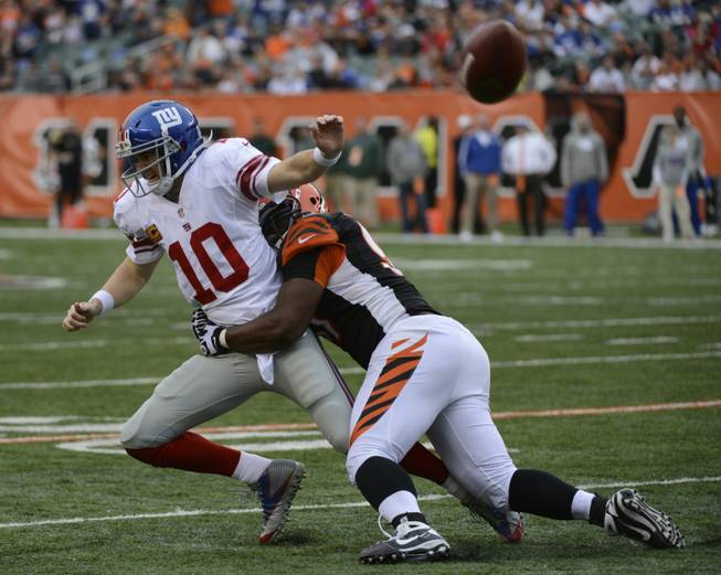 New York Giants quarterback Eli Manning (10) is pursued by Cincinnati Bengals defensive tackle Geno Atkins in the second half of an NFL football game, Sunday, Nov. 11, 2012, in Cincinnati.
