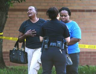 A pair of women react after a stabbing during a fight involving multiple students inside Spring High School Wednesday, Sept. 4, 2013, morning in Spring, Texas.