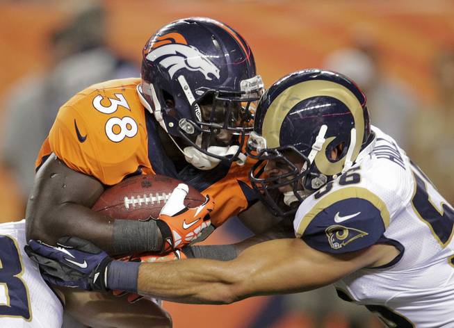 Denver Broncos running back Montee Ball (38) pushes through St. Louis Rams defensive back Robert Steeples (36) in the third quarter of a preseason NFL football game, Saturday, Aug. 24, 2013, in Denver.