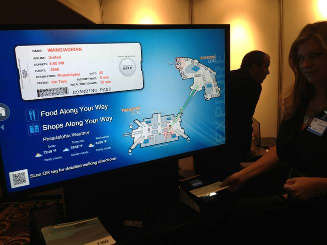 Four Winds Interactive, which has interactive way-finding maps in Las Vegas casinos, has a system that uses a passenger's boarding pass to direct passengers to their gates. Four Winds' Alison Rank demonstrates the system at the Future Travel Experience Global trade show on Sept. 5, 2013.
