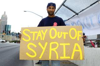 Paul Gones poses with his sign during a protest at the Tropicana Avenue overpass above I-15 Saturday, Sept. 7, 2013. About 50 people attended the protest.
