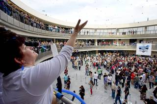 Zappos employee Ana Santiago catches confetti during the grand opening ceremony for the Zappos headquarters in the old city hall building downtown Monday, Sept. 9, 2013. According to RecordSetter, a record was set for the largest number of people (1,577 people) to cut a grand opening ribbon at the same time.