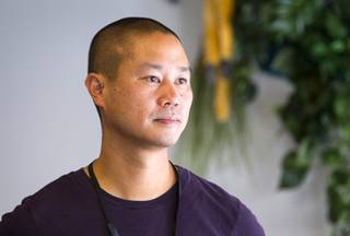 Zappos CEO Tony Hsieh looks out a window from the Monkey Room where he has his office at the new Zappos headquarters in the old city hall building downtown Monday, Sept. 9, 2013. The downtown headquarters officially opened Monday.
