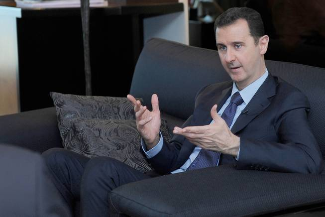 In this Monday, Aug. 26, 2013, file photo released by the Syrian official news agency SANA, Syrian President Bashar Assad gestures as he speaks during an interview with a Russian newspaper, in Damascus, Syria.