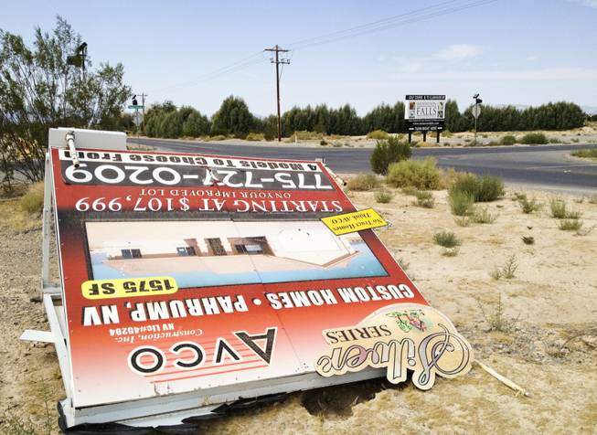 A sign in Pahrump advertising custom homes is knocked over, Monday, Sept. 9, 2013. Behind it is a sign for the master-planned community of Mountain Falls, the only place in Pahrump where subdivisions are being built.