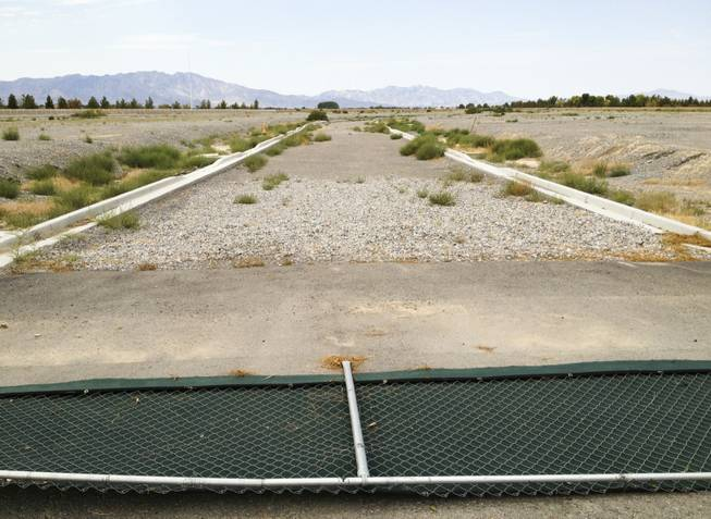 Burson Ranch, a housing development in Pahrump by Beazer Homes, was supposed to have almost 600 homes but only a few dozen were built. Above, a fence is knocked down near an unfinished roadway just inside the main entry of Burson, Monday, Sept. 9, 2013.