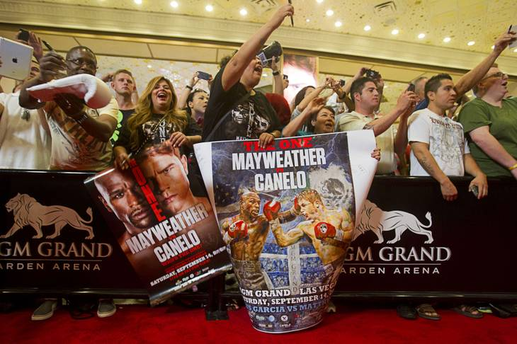 Fans try to get the attention of boxers during grand arrivals at the MGM Grand Tuesday, Sept. 10, 2013. Undefeated boxers Floyd Mayweather Jr. and Canelo Alvarez of Mexico will meet for a WBC/WBA 154-pound title fight at the MGM Grand Garden Arena on Saturday.