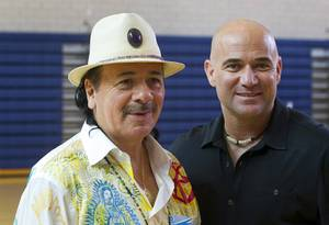 Carlos Santana stands with with Andre Agassi at Andre Agassi College Preparatory Academy on Tuesday, Sept. 10, 2013. Santana brought a surprise donation of 200 instruments for the school's music students. The instruments came from Hermes Music, LP Music and PRS guitars.
