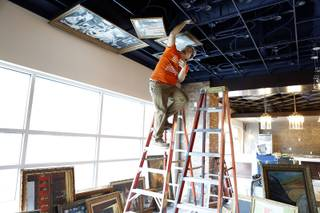 Andy Ruiz of Quality Installation covers the ceiling with paintings at Downtown Grand under construction on Tuesday, September 10, 2013.