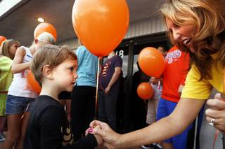 Kelly Thomas-Boyers, the founder of and President of Adam's Place for Grief, gives a balloon to Dov, 3, to write a message to his deceased father for a balloon release at Adam's Place for Grief in Las Vegas on Tuesday, September 10, 2013.