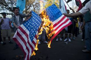 Demonstrators burn a banner that resemble US flags during a protest against a possible military attack by the United States on Syria in front of the US embassy in Buenos Aires, Argentina, Tuesday, Sept. 10, 2013.