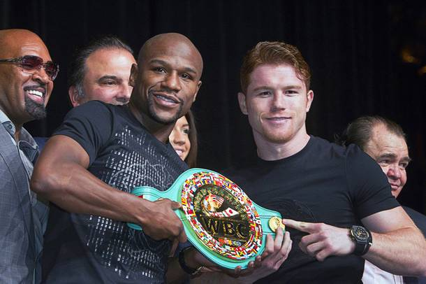 Undefeated boxers Floyd Mayweather Jr., left, and Canelo Alvarez of Mexico pose with a WBC super welterweight belt during a news conference at the MGM Grand Wednesday, Sept. 11, 2013. Mayweather and Alvarez will meet for a WBC/WBA 154-pound title fight at the MGM Grand Garden Arena on Saturday.
