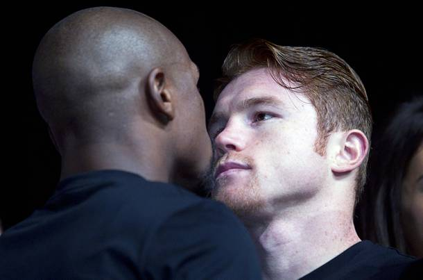 Undefeated boxers Floyd Mayweather Jr., left, and Canelo Alvarez of Mexico face off during a news conference at the MGM Grand Wednesday, Sept. 11, 2013. Mayweather and Alvarez will meet for a WBC/WBA 154-pound title fight at the MGM Grand Garden Arena on Saturday.