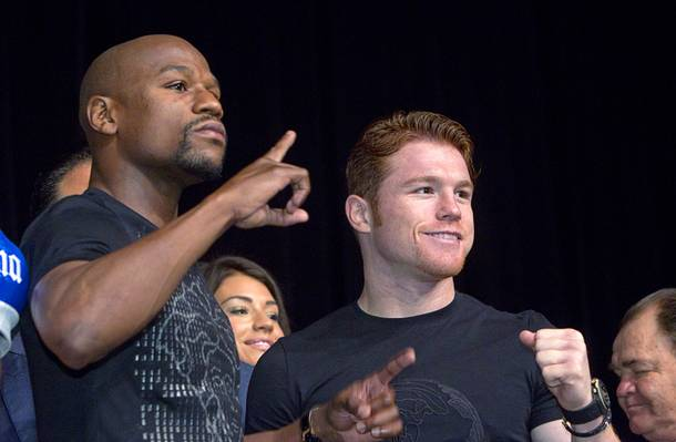 Undefeated boxers Floyd Mayweather Jr., left, and Canelo Alvarez of Mexico pose during a news conference at the MGM Grand Wednesday, Sept. 11, 2013. Mayweather and Alvarez will meet for a WBC/WBA 154-pound title fight at the MGM Grand Garden Arena on Saturday.