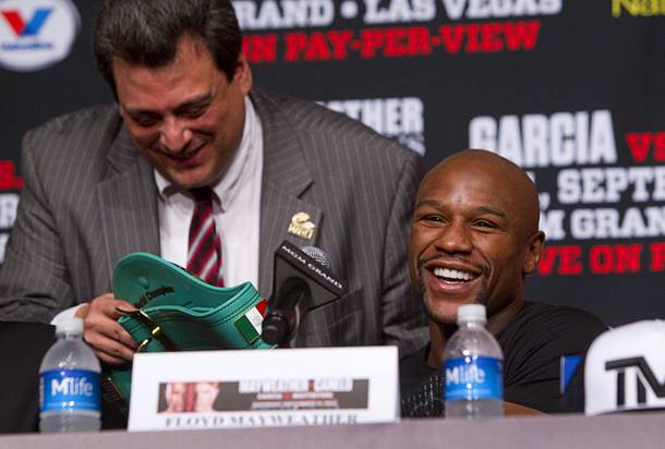 Floyd Mayweather Jr., right, smiles after looking over a WBC super welterweight belt during a news conference at the MGM Grand Wednesday, Sept. 11, 2013. Mauricio Sulaiman, WBC executive director, is at left. Mayweather and Canelo Alvarez of Mexico will meet for a WBC/WBA 154-pound title fight at the MGM Grand Garden Arena on Saturday.