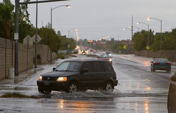 A Honda CR-V drives through storm runoff on El Capitan Way and Peace Way Wednesday, Sept. 11, 2013.