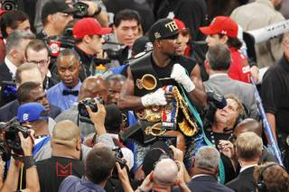 Floyd Mayweather holds his belts after defeating Canelo Alvarez during their super welterweight title fight Saturday, Sept. 14, 2013 at the MGM Grand Garden Arena. Mayweather won the fight with a majority decision.