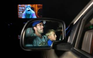 Andrew Whitlock, 34, and his son, Evan, watch the movie,
