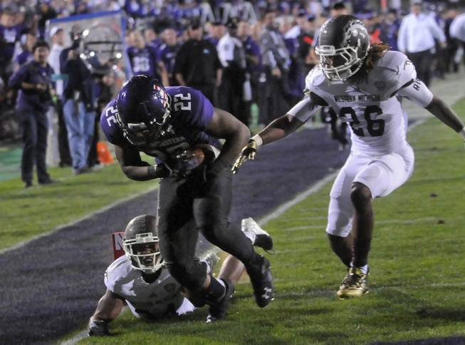 Northwestern's Treyvon Green (22) runs into the end zone after a touchdown against Western Michigan's Donald Celiscar (34) and Trevor Sweeney (25) during the fourth quarter of an NCAA college football game in Evanston, Ill.,  Saturday, Sept. 14, 2013.
